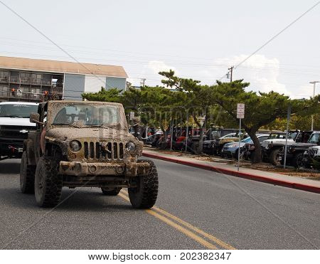 OCEAN CITY MD - AUGUST 26 2017: A vintage Jeep covered thick dried mud arrives at the Roland E. Powell Convention Center on Saturday afternoon of Jeep Week in Ocean City MD.