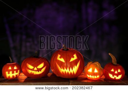 Group of Halloween Jack o Lanterns at night against a spooky forest background
