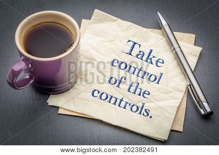 Take control of the controls - handwriting on a napkin with cup of coffee against gray slate stone background