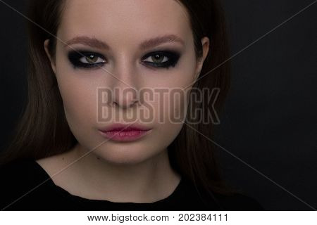 The beautiful woman with a languishing look and brown eyes. Gothic style gloomy fashionable image. Smooth opaque skin smoky eyes and natural lips