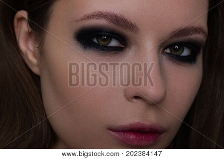 Close up of the woman with a languishing look and brown eyes. Gothic style gloomy fashionable image. Smooth opaque skin smoky eyes and natural lips