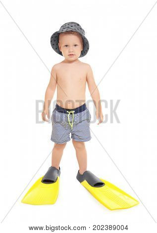 Cute little boy in hat and blue striped swim trunks wearing bright yellow flippers isolated on white