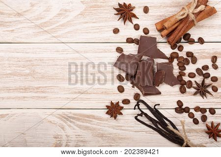 chocolate, vanilla sticks, cinnamon, coffee beans and star anise on white wooden background with copy space for your text. Top view
