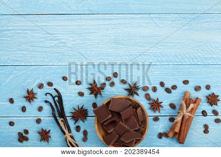 chocolate, vanilla sticks, cinnamon, coffee beans and star anise on blue wooden background with copy space for your text. Top view