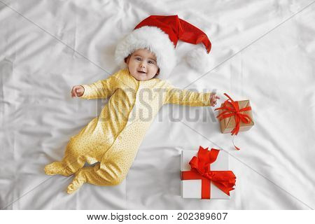 Cute little baby in Santa hat and gift boxes on white sheet