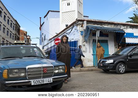 Chefchaouen Morocco - April 10 2016: People in a street with cars and shops in the town of Chefchaouen in Morocco North Africa
