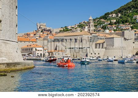 Dubrovnik Croatia - June 9 2017: The Old Harbour at Dubrovnik with the walls of the Old City one of the most prominent tourist destinations in the Mediterranean Sea filled with tourists and boats of all sorts.