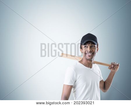 Portrait of an African American young man wearing a white T shirt and a black cap smiling and holding a baseball bat. Gray wall background. Mock up