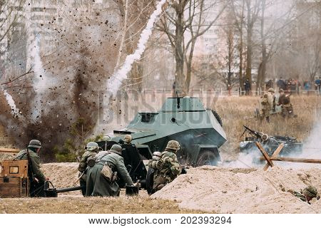 Re-enactors Dressed As German Soldiers In World War II Are Fighting Shooting With A Cannon On The Russian Soviet Armored Car During Historical Reenactment.