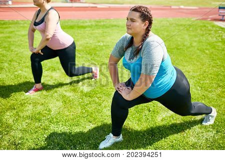 Group of friendly girls stretching legs in knee bend while exercising on green lawn