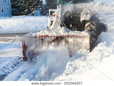 Snow blower attached to a tractor cleaning out a residential driveway.