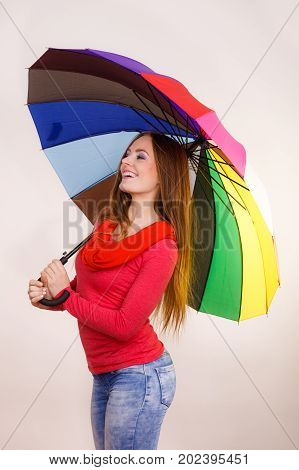 Woman fashionable rainy smiling girl in red clothing standing under colorful umbrella having fun. Meteorology forecasting and weather season concept