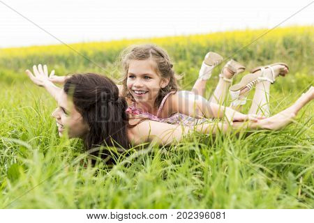 A Happy family mother and child daughter embrace on yellow flowers on nature in summer