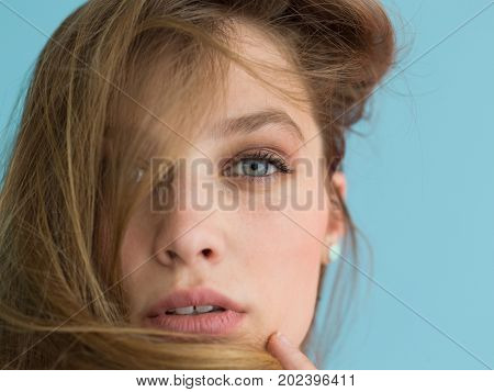 Portrait of a beautiful positive young woman while playing with her long silky hair isolated on blue background