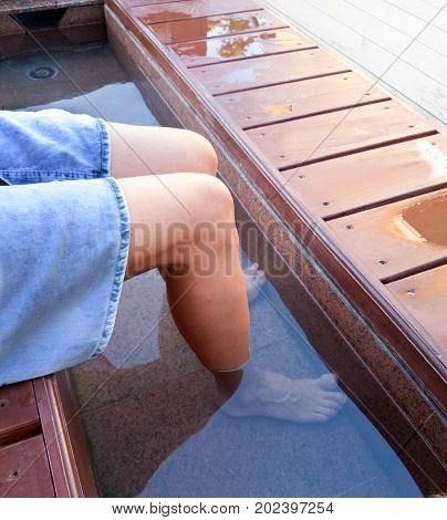 woman hovers her feet in the open city onsen at the bus stop YonagoJapan