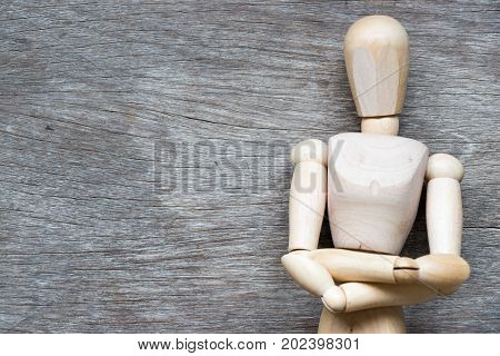 Man figure posing in fold one's arms over the chest on wooden background with copy space (Concept for business thinking planning)