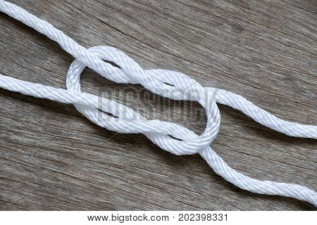 White rope in reef knot shape on wood background