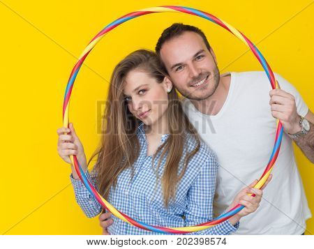portrait of happy couple with hula hoop isolated on yellow background