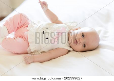 A Baby Girl Laying on a White Bed