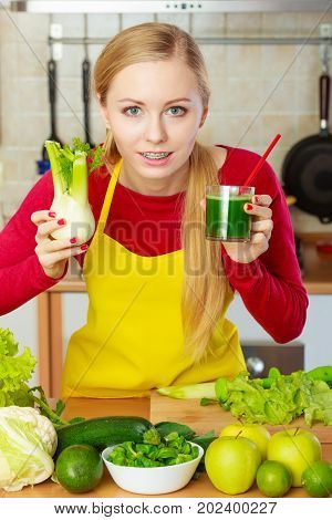 Woman In Kitchen Holding Vegetable Fennel Smoothie Juice