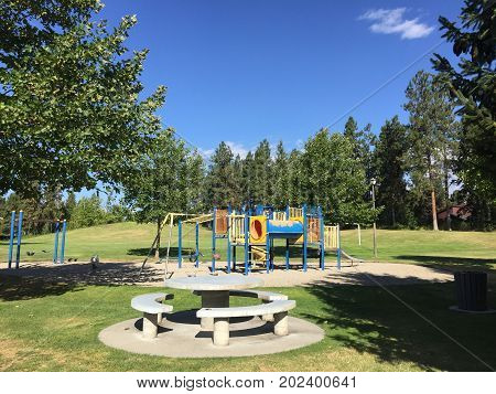Playground with round concrete seating area. Swing set and colorful climbing play set in grass field with tall trees and clear blue sky.