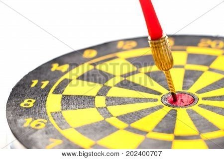 Yellow and black color dartboard with number and have the dart hit at red dot on white background (Concept for business focus)