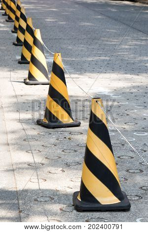 Yellow and black color traffic cone with the rope to guide the permission area on concrete background