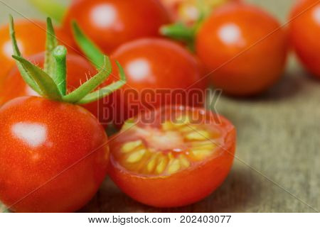 Fresh cherry tomato on rustic wood table. Close up lovely cherry tomato for background or wallpaper. Prepare fresh cut cherry tomato for home cooking look so delicious. Macro concept with copy space. Cherry tomato in fresh vegetable concept