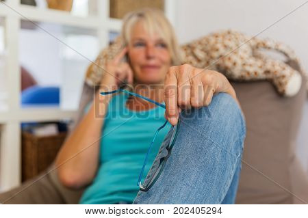 Mature Woman Lies On A Seating Furniture While She Takes A Phone Call