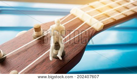 Miniature figurine Businessman sitting relax on ukulele. Ukuleles is member of lute family of instruments with nylon stringed usually played with bare thumb or fingertips. Concept of Music Education.