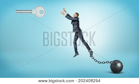 A businessman chained to an iron ball tries to jump and reach a large silver key hanging above. Effort to reach your dream. Key to success. Get free.