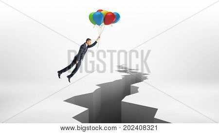 A businessman flies over a huge rift on white surface while holding a bunch of colorful balloons. Crisis management. Business consulting. Avoid trouble.
