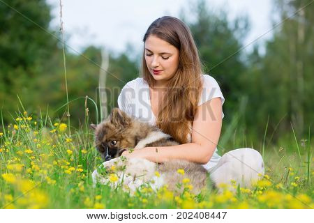 Young Woman Sits With An Elo Puppy In The Grass