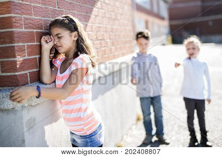 sad moment Elementary Age Bullying in Schoolyard