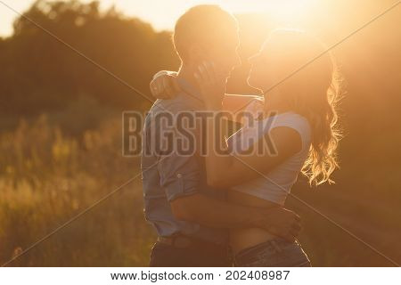 Loving couple at sunset. Guy hugs girl. They look into each other's eyes. Face to face. Love and romance. Young and happy.