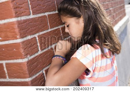 A six years old school girl cry beside brick wall