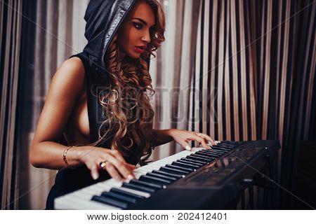 Young woman musician sensual fashion portrait. Playing piano in  night interior.