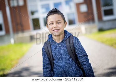A student boy outside at school standing and smiling