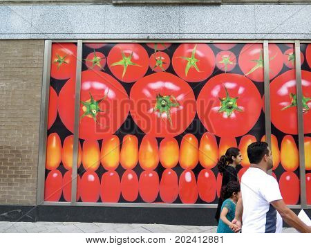 Reading England - August 4 2017: Family walking past tomato advert in main street of English Market town