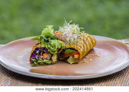 Raw vegan carrot and cumin wrap roll stuffed with shred lettuce tomato avocado spinach and savory zucchini hummus . Island Bali Ubud Indonesia
