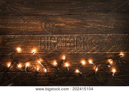 Christmas lights bulb on wood table. Merry christmas (xmas) background. topview border design - rustic and vintage styles