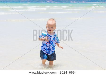 Cute Asian 1 year old toddler baby boy child standing / playing on white sand beach Family travel water outdoor activity on summer beach vacation with childrenThailand Selective focus cool tone