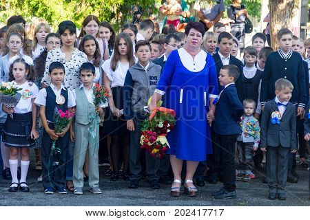 Adygea Russia - September 1 2017: children with bouquets of flowers enrolled in the first class at school with teachers and high school students at the solemn opening of the school year in the day of knowledge