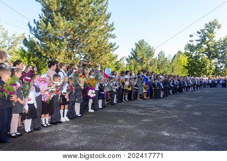 Adygea Russia - September 1 2017: children with bouquets of flowers enrolled in the first grade in school with teachers and pupils on a solemn ruler of the school year on knowledge day