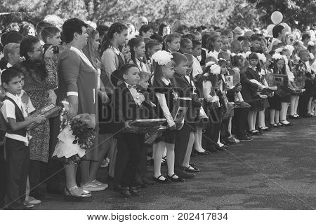 Adygea Russia - September 1 2017: children with bouquets of flowers enrolled in the first grade in school with teachers and pupils on a solemn ruler on knowledge day a black and white photo