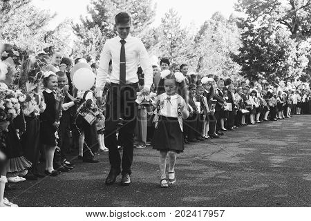 Adygea Russia - September 1 2017: a pupil of the senior class and a girl first-grader with a bell in hands on a school solemn line in the day of knowledge black and white photo