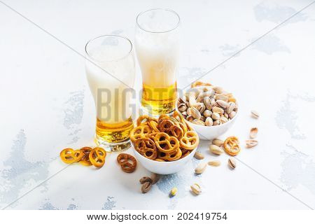 Beer in glass, mini pretzel and pistachio on white stone background. Copy space