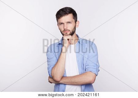 Young serious Caucasian man in shirt holding hands on his chin looking with thoughtful and skeptical expression on his face suspecting of something hesitating to make decision. Body language.