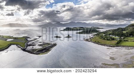 Aerial view of Loch Laich with the historic castle Stalker in the background in ArgyllScotland