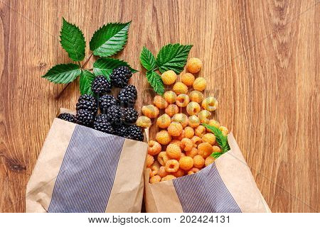 On the wooden table are two paper bags with scattered yellow raspberries large blackberries and green leaves.